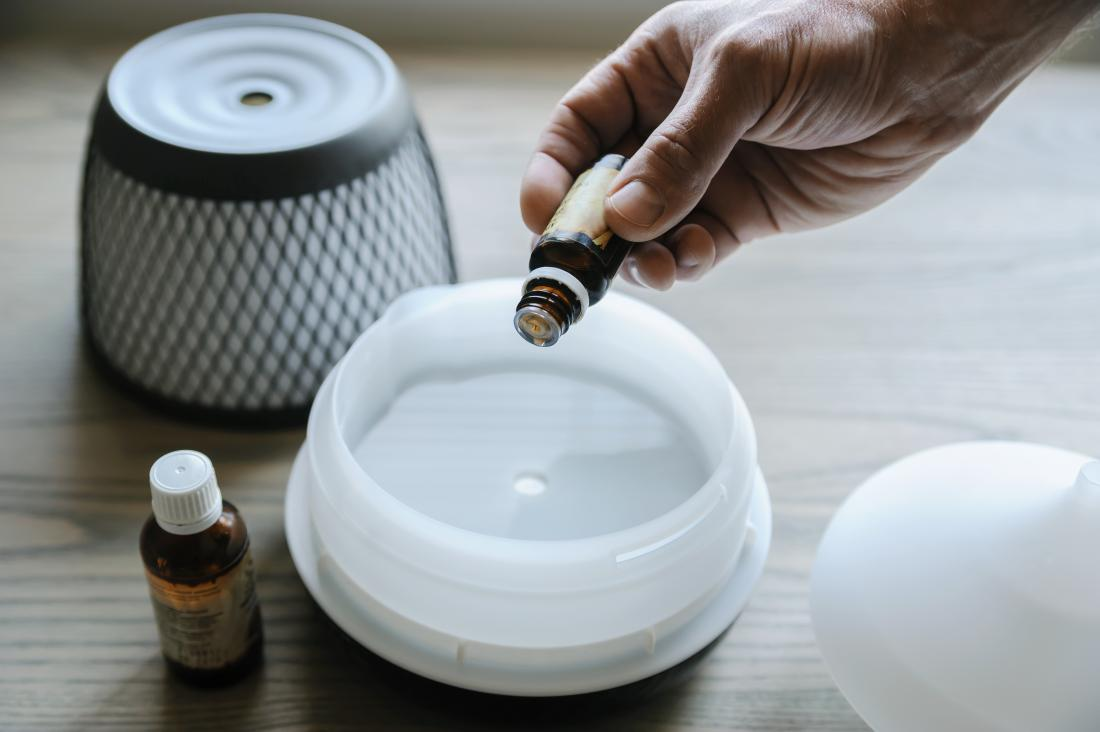 Person putting essential oil into aromatherapy diffuser
