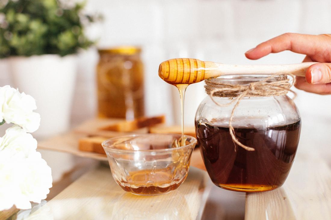 Raw honey in jar on wooden table