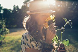 A person smells a sunflower.